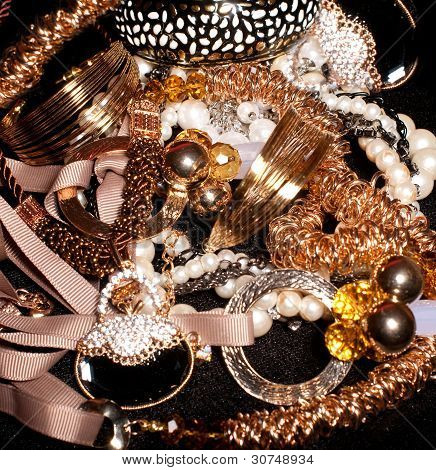 collection of gold jewelry on a black background