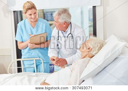 Doctor and nurse with clipboard while visiting a patient's bed