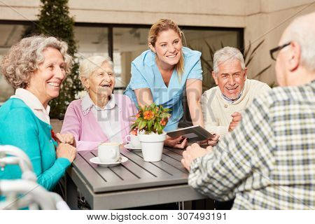 Group of seniors and caregiver using tablet computer while having coffee