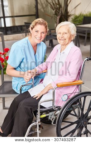 Caring geriatric nurse and disabled elderly woman in wheelchair at nursing home