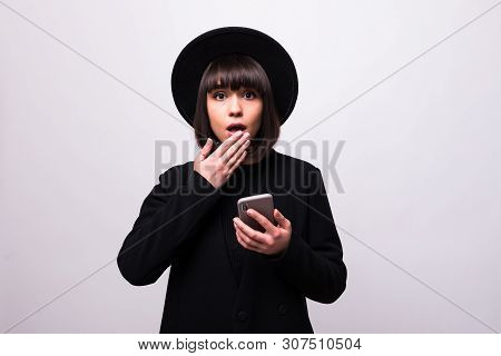 Portrait Of Shocked Young Woman In Black Hat Looking At Mobile Phone Isolated Over White Background