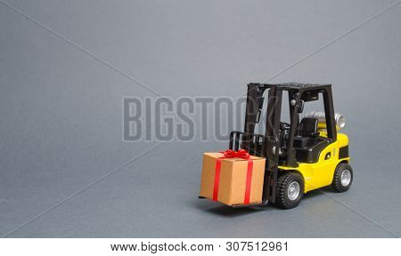 Yellow Forklift Truck Carries A Gift With A Red Bow. Purchase And Delivery Of A Present. Retail, Dis