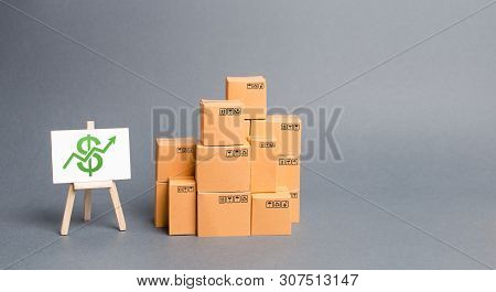 Lots Of Cardboard Boxes And Stand With Green Up Arrow. Growth Of Income From The Sale Of Goods. Pric