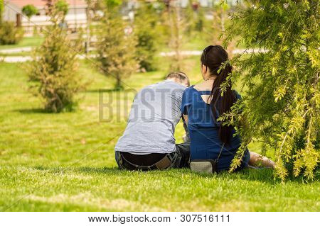 Back Side Of A Young Couple Sitting On The Grass In A Park On A Sunny Day. Casual Lifestyle Concept.