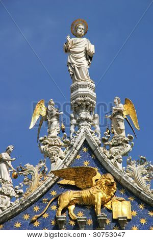 Vertical oriented image of sculptures on the rooftop of San Marco Basilica against blue sky in Venice, Italy.