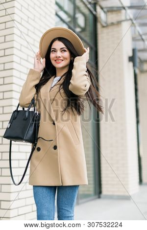 Pretty Smiling Brunette Girl With Bag In Coat And Hat Walking On The Street