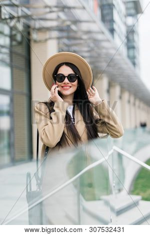 Excited Young Woman Wearing Coat And Eyeglasses Using Mobile Phone While Walking Through City Street