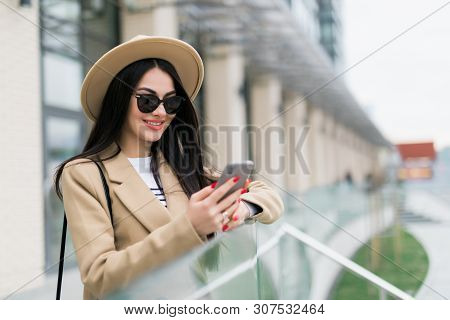 Beautiful Girl In A Beige Coat, Holds A Smartphone In Her Hands, Stands In Front Of The Building's U
