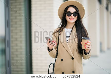 Pretty Girl Stand On The Street Use Phone And Drinking Coffee