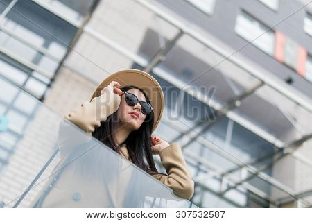 Young Cheerful Woman In Hat And Coat Standing On Balcony And Smiling Outdoors. Beautiful And Fashion