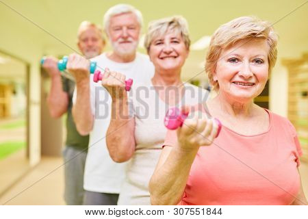 Vital seniors group trained with dumbbells in the fitness center for muscle growth and strength