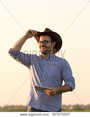 Satisfied Farmer With Hat Holding Tablet In Field
