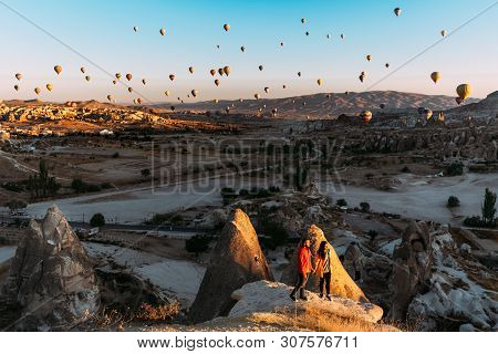 Man And Woman Greet The Dawn Among Balloons. Couple In Love Among Balloons.  Travelers In The Mounta