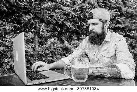 Taking The Online World And Beer Mug With Him. Computer Keyboard Operator. Computer User Drinking Be