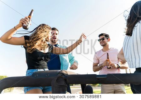 Young Pals Dancing And Enjoying Music With Beer On Road Trip In Summer