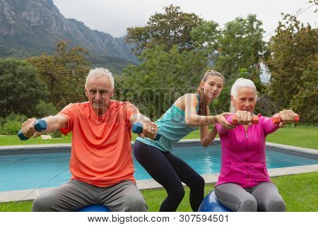 Front view of Caucasian female trainer assisting active senior Caucasian couple to exercise with dumbbells in the backyard