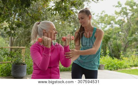 Front view of beautiful Caucasian female trainer assisting active senior Caucasian woman to exercise with dumbbell in the porch