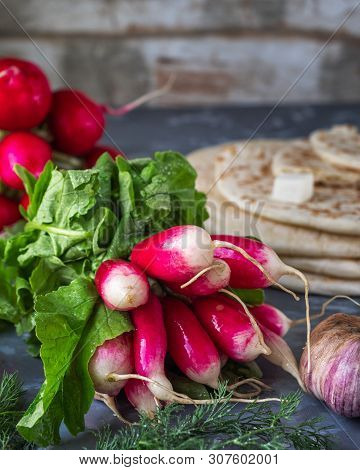 A Bunch Of Fresh Red Radish, Garlic Head On A Gray Background Shot From Close Range