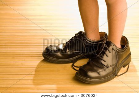 Big Shoes To Fill, Child'S Feet In Large Black Shoes, On Wood Floor