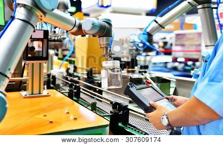 Engineer Check And Control Automation Robot Arms Arranged Glass Water Bottle On Automatic Industrial