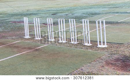 A Close Up View Of Seven White Metal Cricket Wickets All In A Row On The Field Ready For Practice