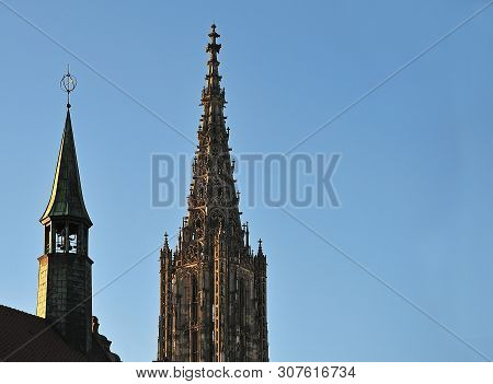 View To Steeple Of Gothic Minster In Ulm, Germany With Belltower Of Historic Town Hall In Foreground