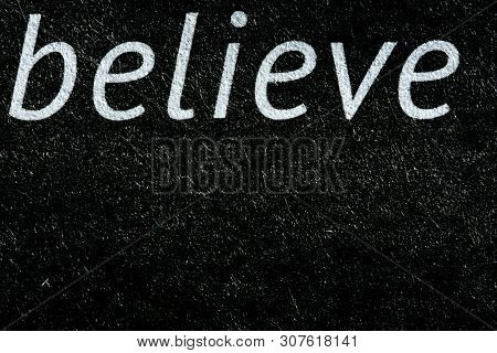 Macro Image Of The Word Believe On Newsprint In Black And White