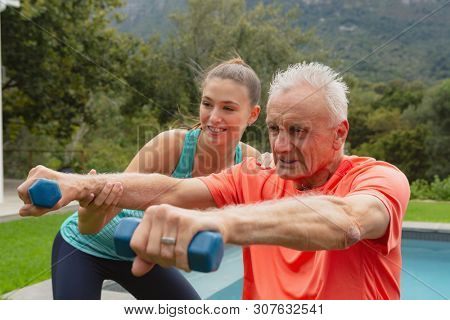 Side view of Caucasian female trainer assisting active senior Caucasian man to exercise with dumbbells in the backyard