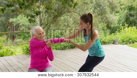 Side view of beautiful Caucasian female trainer assisting active senior Caucasian woman to exercise in the porch