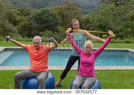 Front view of Caucasian female trainer assisting active senior Caucasian couple to exercise with resistance band in the backyard