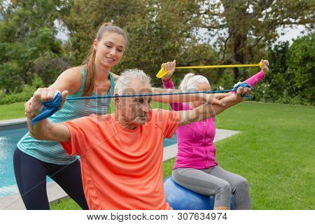 Side view of Caucasian female trainer assisting active senior Caucasian couple to exercise with resistance band in the backyard