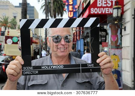 6-18-2019 Hollywood, California: A man wears silver reflective sunglasses while posing with a Hollywood Movie Click Board while on the streets on Hollywood California. Editorial Use Only.