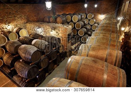 Rows Of Alcoholic Barrels Are Kept In Stock. Distillery. Cognac, Whiskey, Wine, Brandy. Alcohol In B