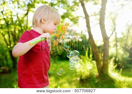 Cute Little Boy Is Playing With Big Bubbles Outdoor. Child Is Blowing Big And Small Bubbles Simultan
