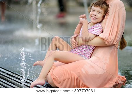 Portrait Of Beautiful Disabled Girl In The Arms Of His Mother Having Fun In Fountain Of Public Park