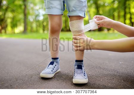Mother Hands Applying Antibacterial Medical Bandage On Child's Knee After Falling Down.