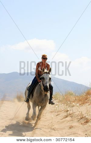 Beautiful blonde woman in bikini  Greece riding a white horse poster