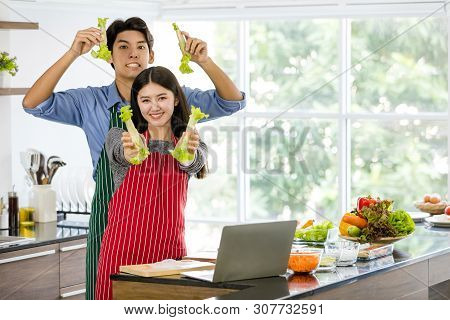 Couple In Apron Make Salad Rolls Together..