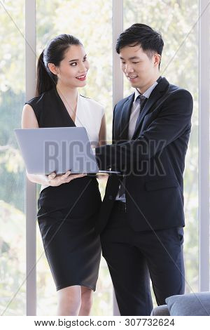 Asian Business People Standing,  Woman Holding Laptop In Her Hand , Man Checking Report From Screen