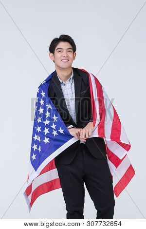 Portrait Of Young And Handdome Happy Asian Man Holding And Covered With American Flag.