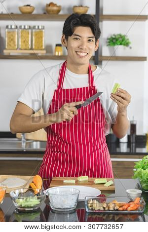 Close Up Shot Of Asian Man In Red Apron, He Cutting Cucumber Into Small Pieces, Vegetable And Ingred