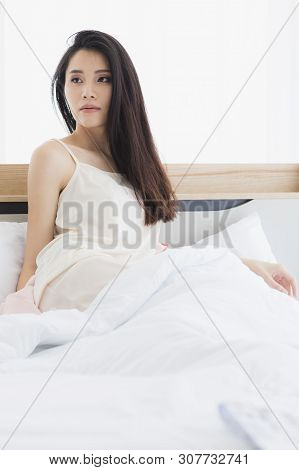Beautiful Asian Woman Model Sitting And Posing On Bed In Sexy Pajamas In Bedroom.