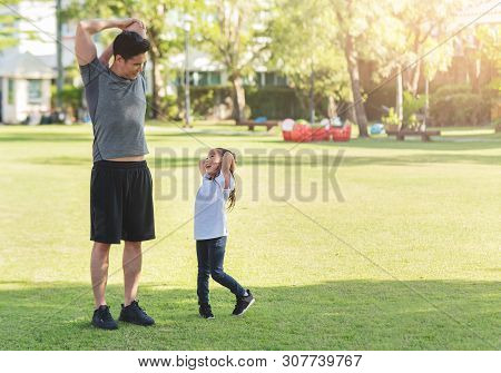 Asian Father And His Daughter Stretching Their Arms And Shoulders Before Exercising. Workouts And Li