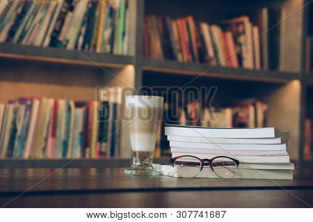 Eyeglasses Lying On Book And Coffee Drink In Library Room With Copy Space For Text Against Bookshelf