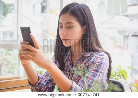 Young Woman Typing Text Message On Smart Phone In Modern Cafe. Asian Girl Sitting At Table Using Mob