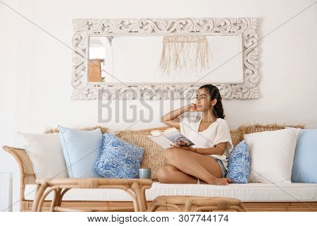 Dreamy Attractive Young Tanned Woman Traveler Relaxing After Tourist Trip Sit Hotel Room Sofa Contem