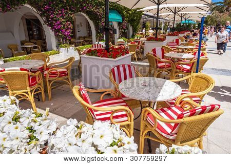 Mallorca, Spain - May 6, 2019: Tables And Chairs In Seaside Restaurant In Port De Pollenca (puerto P
