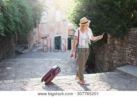 Girl Traveler Looks At City Map With Suitcase At Town Street In Europe. Woman Tourist Is Searching A