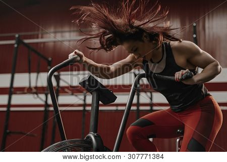 Woman Doing Intense Cardio Training On Exercise Bike. Her Hair Is Flying From The Air Flow. Copy Spa