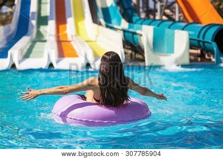 Pretty Brunette Woman In Black Bikini Sitting On The Rubber Ring In The Pool. Summer Vacation. Enjoy